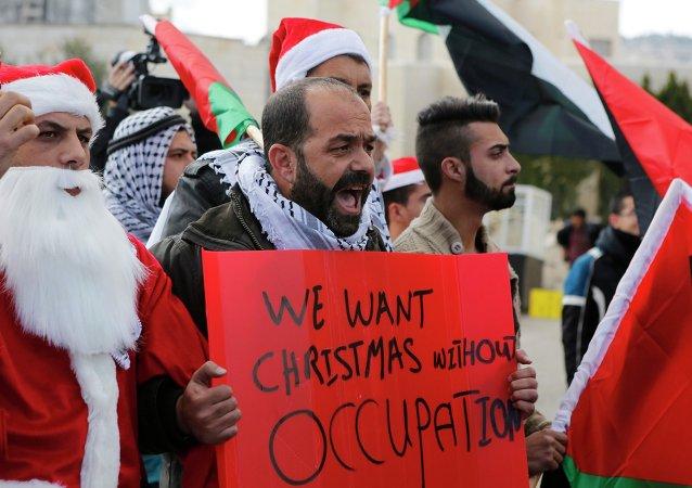 Manifestantes palestinos, vestidos de Papá Noel, se han enfrentado este martes a las fuerzas de seguridad israelíes en la localidad cisjordana de Belén, 23 de diciembre,2014