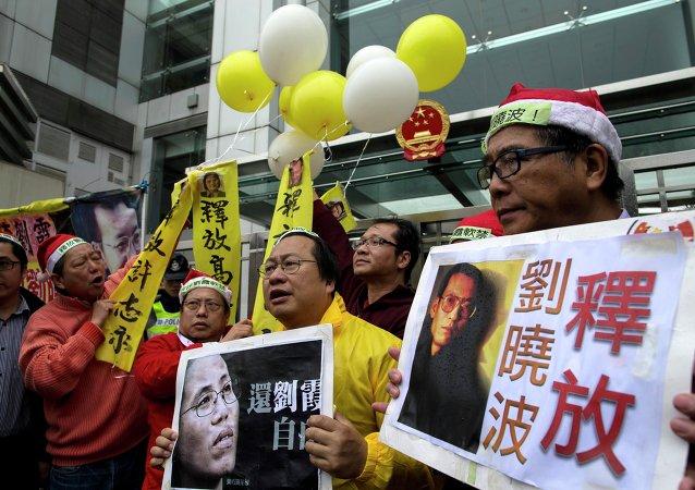 Manifestantes con los carteles del premio Nobel de la Paz Liu Xiaobo y a su mujer Liu Xia