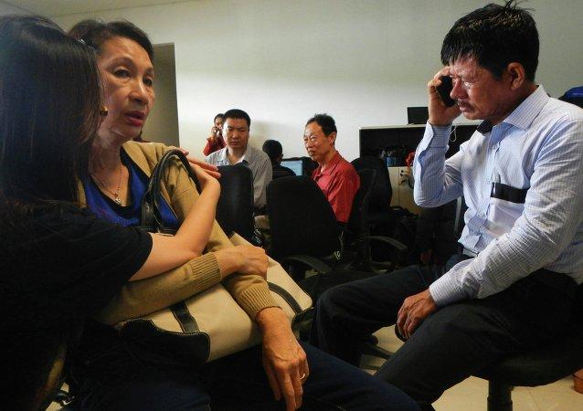 Family members of passengers on board AirAsia flight QZ 8501wait for information inside a crisis centre at Juanda Airport in Surabaya