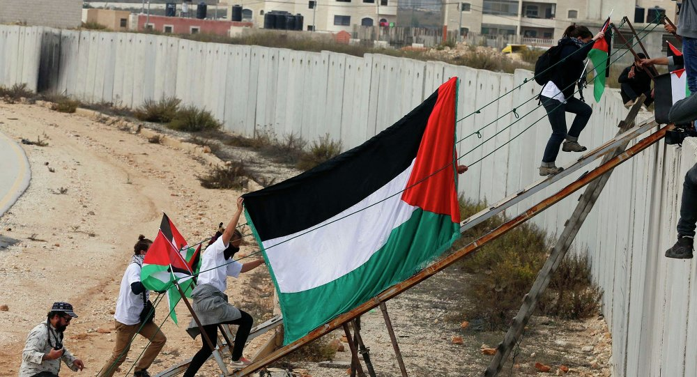 Foreign activists and Palestinian protesters use a metal ramp to cross over a section of the controversial Israeli barrier during a protest over tension in Jerusalem, near the Israeli Qalandia checkpoint between the West Bank city of Ramallah and Jerusalem November 14, 2014.