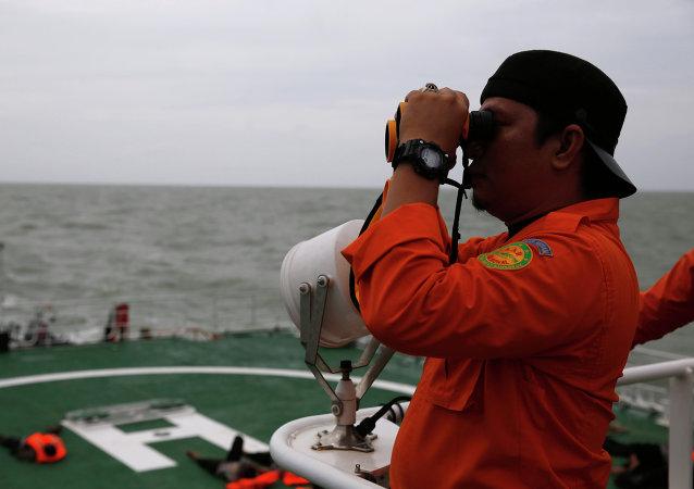 Член спасательной команды в ходе поисковой операции пассажиров и обломков боинга AirAsia 2 января 2015
