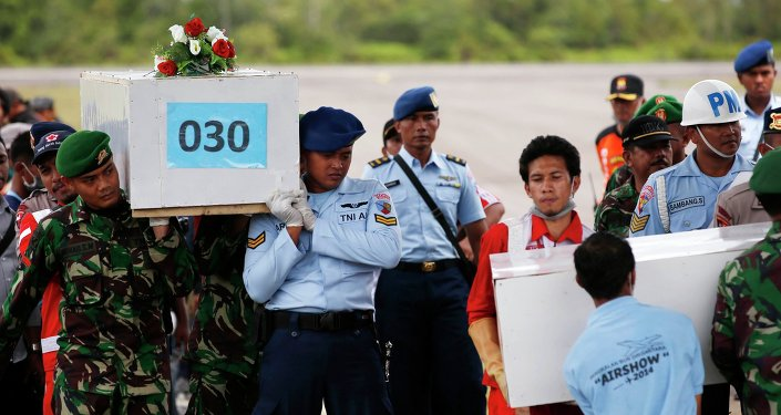 Caskets containing the remains of passengers from AirAsia QZ8501 are carried into an Indonesian military cargo plane