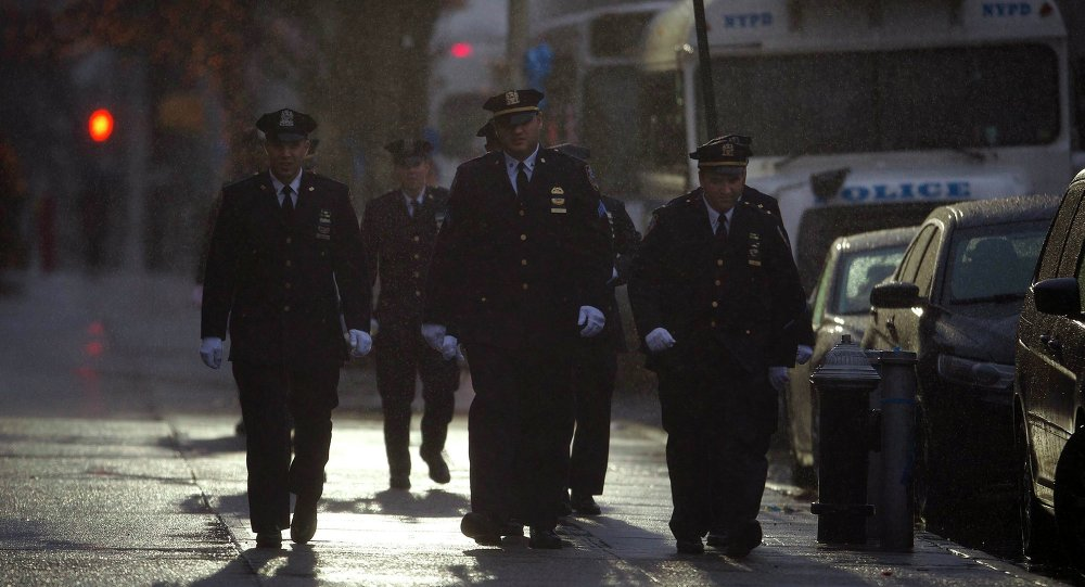 Police officers walk in the rain to attend slain New York Police Department officer Wenjian Liu's wake in the Brooklyn borough of New York January 3, 2015.