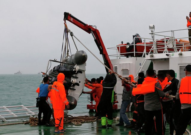 Rescue team members and policemen lift a boat up onto the deck of the Search and Rescue (SAR) ship KN Purworejo during a search operation for passengers onboard AirAsia Flight QZ8501 in the Java Sea January 4, 2015.