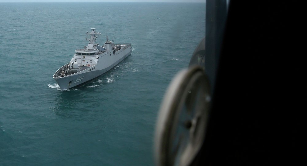 Indonesian navy ship KRI Sultan Hasanudin is seen through the window of a Super Puma helicopter during a search operation for passengers onboard AirAsia Flight QZ8501, off the Java sea, in Indonesia January 7, 2015