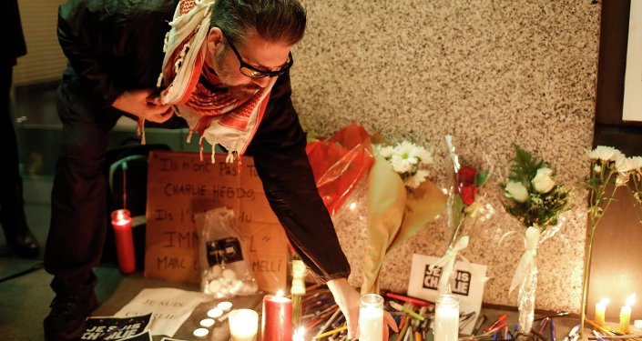 A man places a candle at a makeshift memorial outside the Consulate General of France during a vigil to pay tribute to the victims of an attack on satirical magazine Charlie Hebdo in Paris, in San Francisco, California January 7, 2015