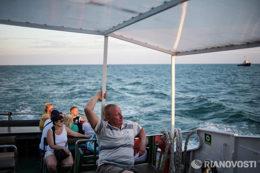 Отдыхающие во время морской прогулки вдоль сочинского побережья