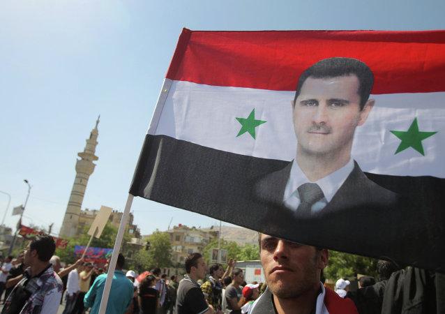 Bandera siria con imagen de Bashar al-Asad (archivo)