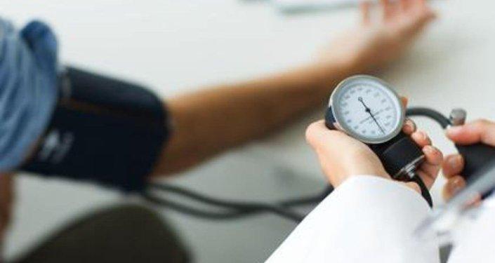 Doctor está mediando la tensión arterial de un paciente