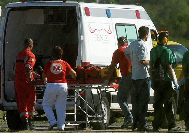 A person rescued from the Cidade de Sao Mateus, a floating oil production, storage and offloading ship (FPSO), is wheeled to an ambulance by paramedics at the Eurico de Aguiar Salles airport in Vitoria