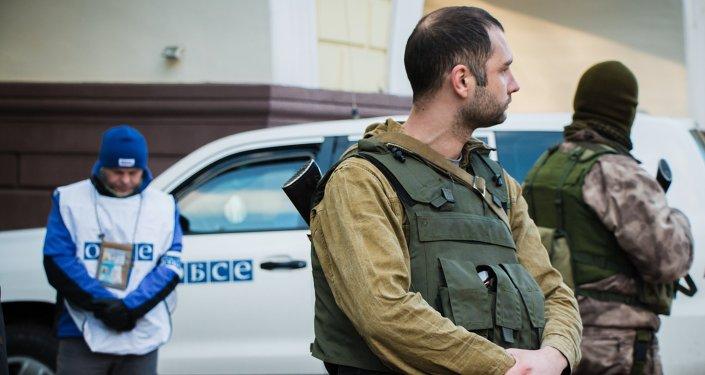 Observador de la OSCE y milicianos de la RPD