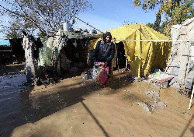 Hombre palestino rescata sus pertenencias de su vivienda después de que fue inundada por el agua de lluvia
