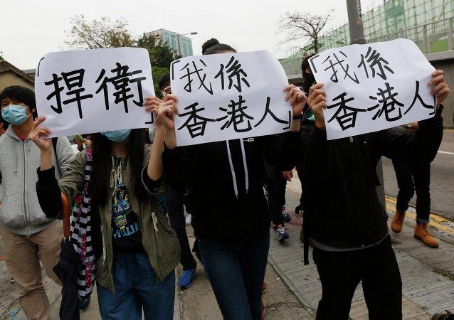 Manifestantes con los cartel donde se escribo Protección y Soy de Hong Kong, 1 de marzo, 2015