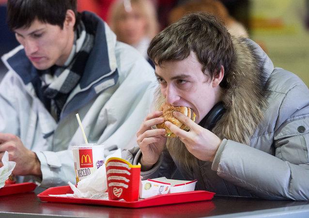 Un hombre come una hamburguesa de McDonald's
