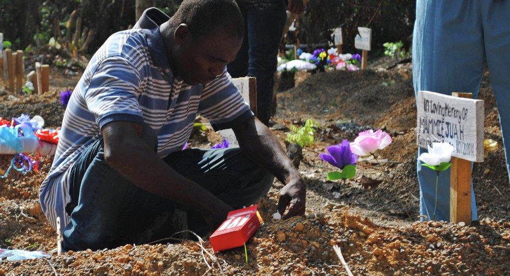 Sobreviviente del virus Ébola Stanley Juah llora en la tumba de su hijo en un cementerio para las víctimas de Ébola