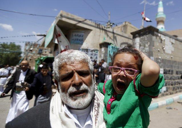 Un hombre lleva en brazo a una niña herida en ataque en la mezquita de Saná