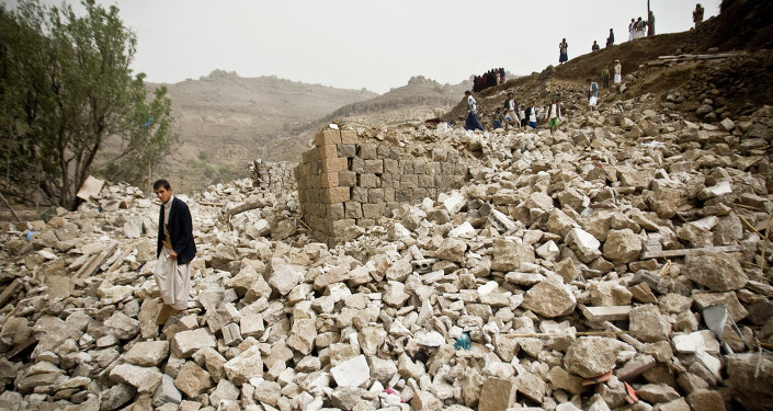 Yemenis stand amid the rubble of houses destroyed by Saudi-led airstrikes in a village near Sanaa