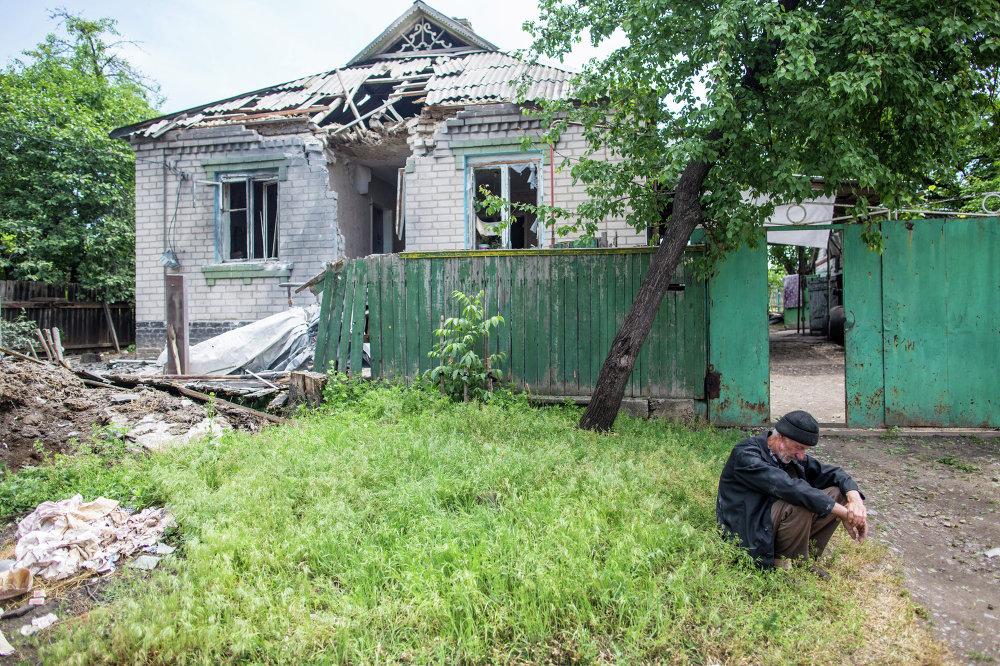 Un hombre de edad junto a su vivienda, destruida por un impacto de proyectil disparado por tropas ucranianas, en el pueblo de Chervoni Molochar cerca de Slaviansk (29 de mayo de 2014)