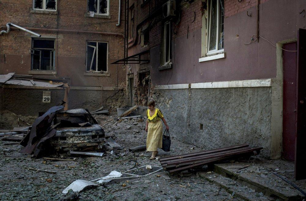 Una mujer junto a su casa, destruida por la artillería ucraniana en Lugansk (20 de julio de 2014)