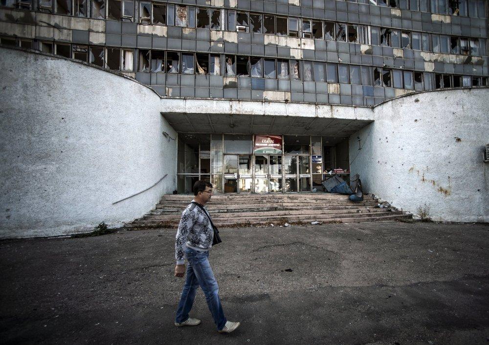 Un vecino de Lugansk pasa frente a un edificio destruido por los bombardeos (13 de septiembre de 2014)