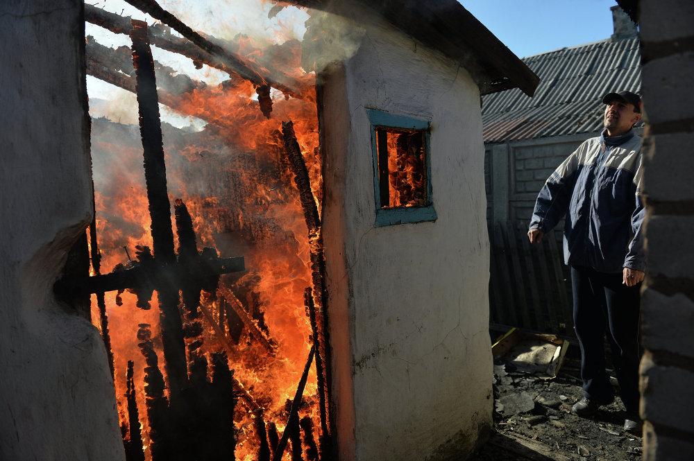 Un vecino de Donetsk junto a su vivienda, destruida y envuelta en llamas tras un bombardeo del Ejército ucraniano (9 de noviembre de 2014)