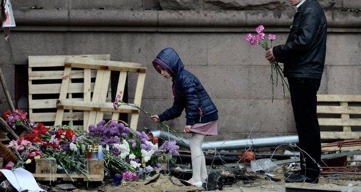 Una niña y un hombre ponen flores en memoria de los quemados en la Casa de los Sindicatos de Odesa