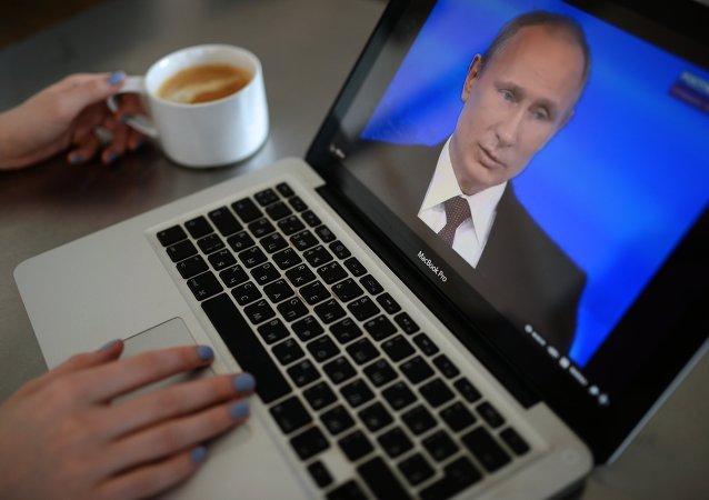 Una mujer esta viendo la emisión de la línea directa con Vladímir Putin