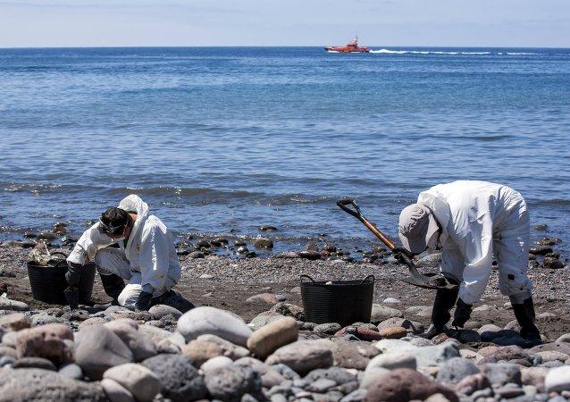 Hombres recogen combustible en la playa Veneguera en Gran Canaria