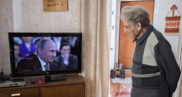 Un hombre mira 'Línea directa' con el presidente de Rusia Vladímir Putin
