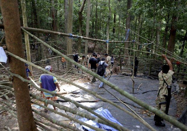 Fuerzas de seguridad y los equipos de rescate inspeccionan en el campamento abandonado en una selva en Tailandia