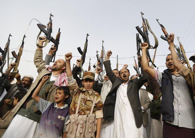 Seguidores del movimiento hutíes levantan sus rifles mientras gritan eslóganes contra los ataques aéreos saudíes en Saná