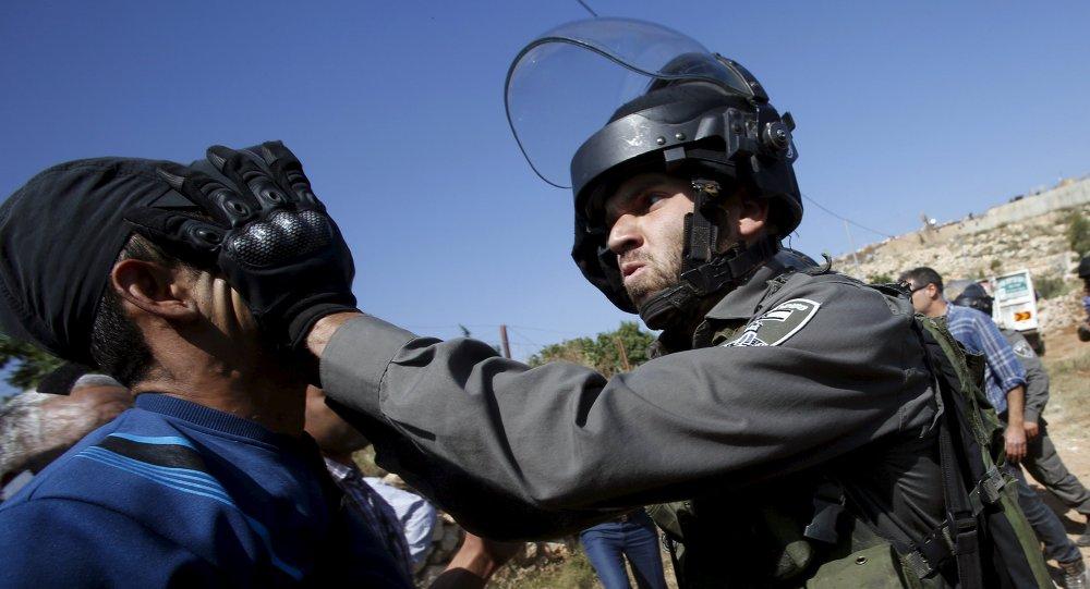 Un policía israelí golpea a un palestino en Cisjordania