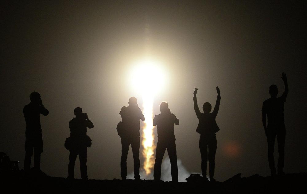 Unas personas contemplando el lanzamiento desde Baikonur a la EEI del cohete Soyuz-FG con la nave pilotada Soyuz TMA-13M y los miembros de las expediciones espaciales 40/41