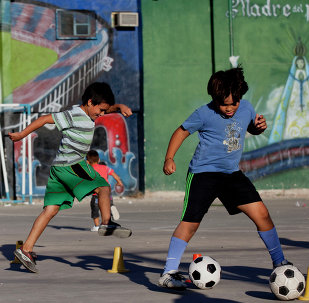 Children play soccer in front a mural of Pope Francis at the 1-11-14 slum in Buenos Aires, Argentina, Thursday, March 13, 2014