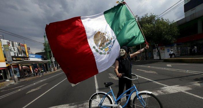Un manifestante por el caso Ayotzinapa lleva una bandera mexicana