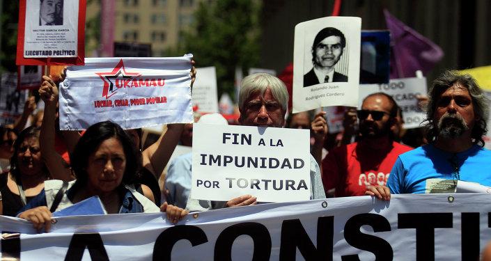 Manifestantes mantienen carteles con fotos de víctimas de la dictadura de Augusto Pinochet (archivo)