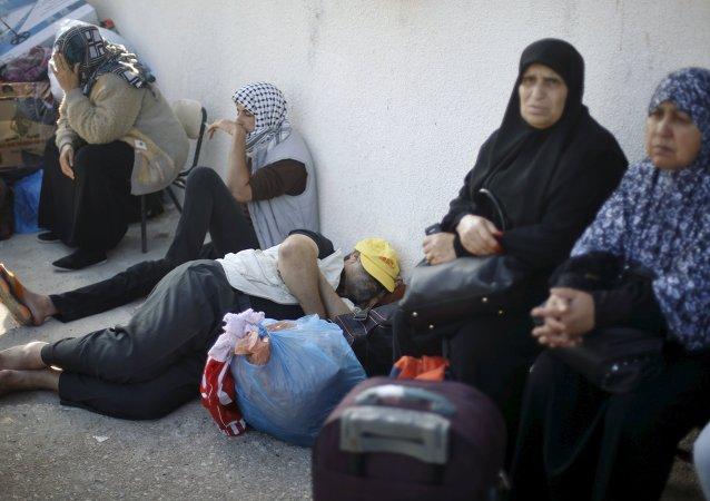 Palestinos esperan el permiso para cruzar la frontera entre Gaza y Egipto Junio 2015