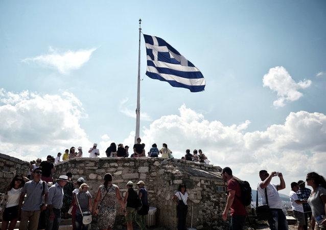 Bandera de Grecia cerca de Acropolis en Atenas