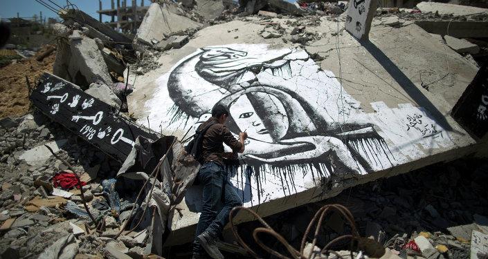 Un palestino dibuja un grafiti en conmemoración de Nakba, éxodo palestino tras la creación del Estado de Israel en el 1948