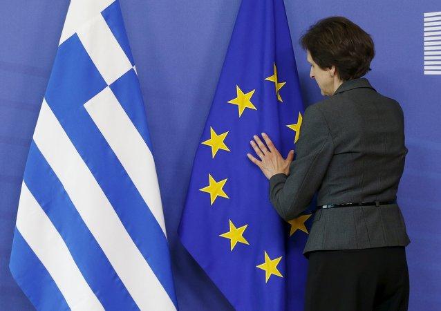 Una mujer ajusta las banderas de UE y Grecia