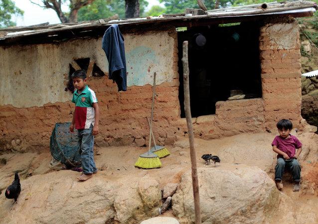 Niños permanecen frente a su humilde hogar en El Magueyito, estado de Guerrero, México, el 19 de julio de 2015