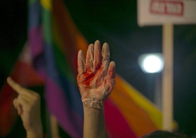 Manifestante levanta el mano en un guante cubierto de sangre falsa durante protestas contra violencia contra comunidad gay en Israel