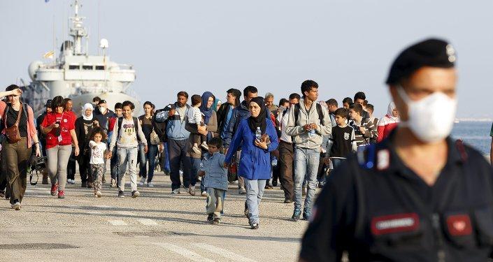 Refugiados sirios acompañados por carabineros italianos después de desembarcar en Augusta, Italia
