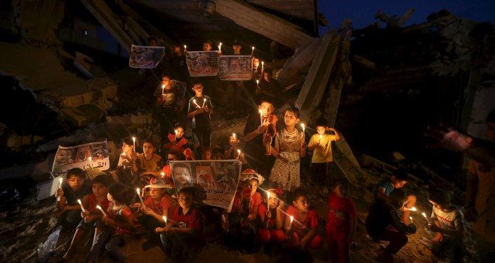 Niños palestinos encienden las velas para recordar un bebé que fue matado por los colonos judíos