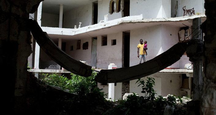 Un padre sostiene a su hija fuera de su habitación en Puerto Príncipe