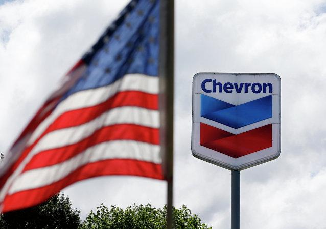 Bandera de EEUU y el logotipo de la petrolera Chevron