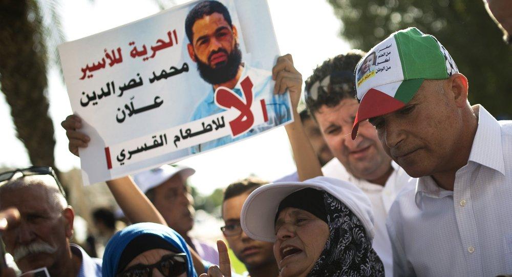Familiares protestan contra alimentación a la fuerza de prisionero palestino Mohammed Allan, visto en el póster