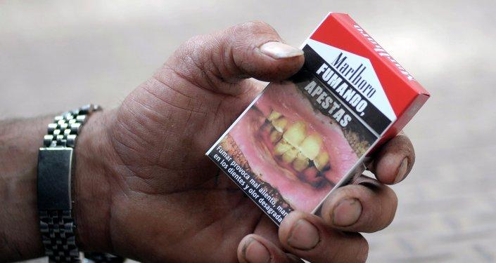 Cajetilla de cigarrillos con una advertencia 'Fumando, apestas'