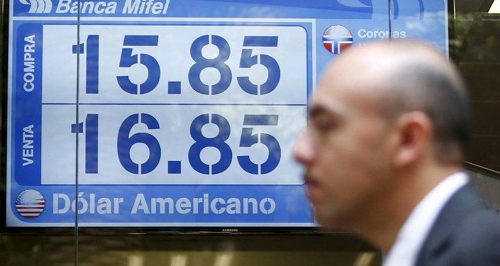 Un hombre está pasando enfrente de un marcador con las tasas de peso mexicano y dólar estadounidense