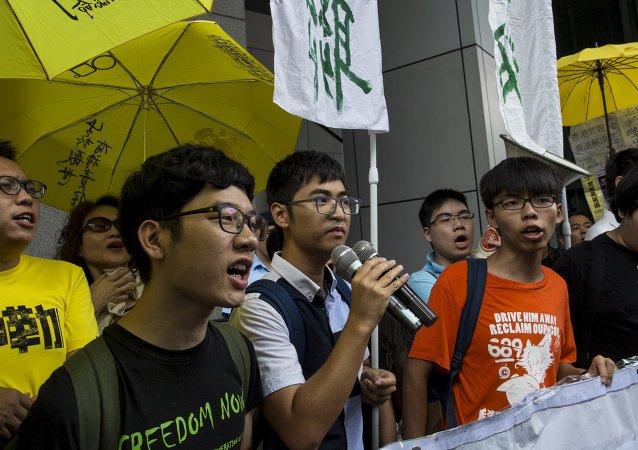 Líderes estudiantiles Nathan Law, Alex Chow y Joshua Wong al llegar a la jefatura de policía de Hong Kong